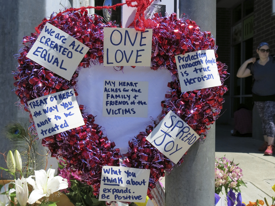A heart-shaped wreath covered with positive messages hangs on a traffic light pole Saturday at a memorial for two bystanders who were stabbed to death Friday on a light-rail train in Portland, Ore. (Gillian Flaccus/AP)