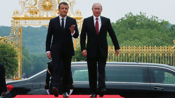 French President Emmanuel Macron and his Russian counterpart, Vladimir Putin, arrive at the Palace of Versailles near Paris on Monday. It