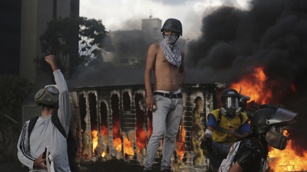 A truck burns behind a man perched near a traffic barrier in Caracas, Venezuela, on Saturday. In more than 60 days of unrest, at least 60 people have died in violence related to protests against President Nicolas Maduro.