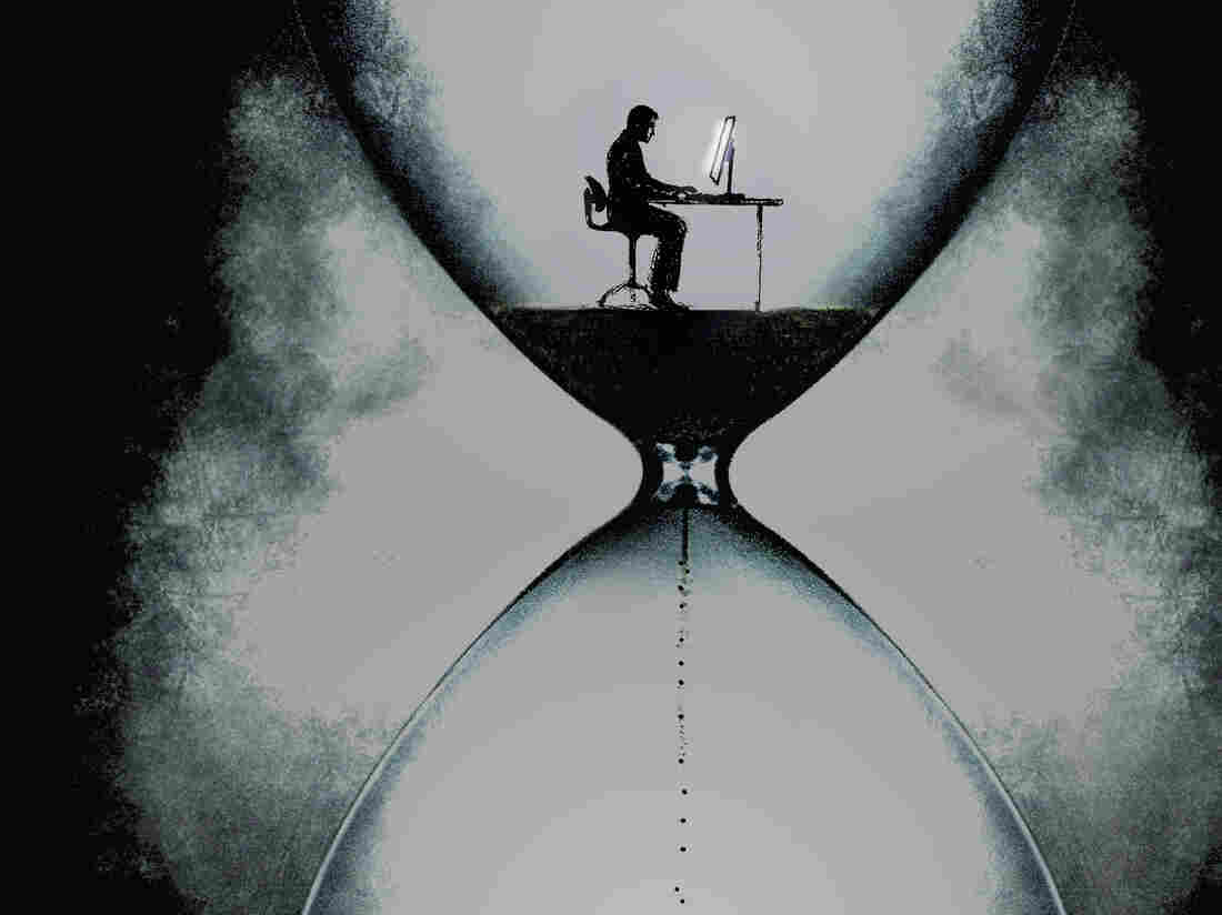 Businessman at desk in an hourglass.