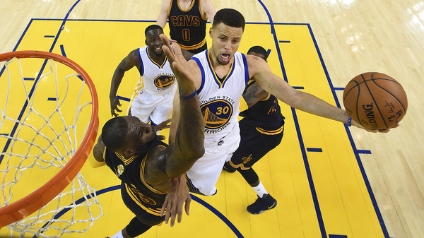 Golden State Warriors guard Stephen Curry shoots against Cleveland Cavaliers forward LeBron James during last year