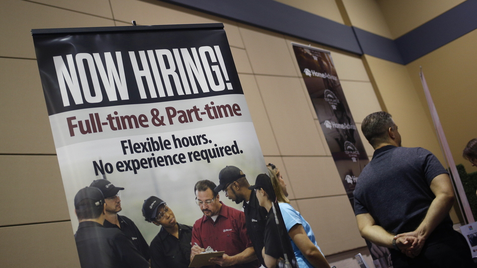 "A ""Now Hiring!"" sign is displayed next to the Jiffy Lube International booth at a jobs fair in Overland Park, Kan., in March. (Bloomberg via Getty Images)"