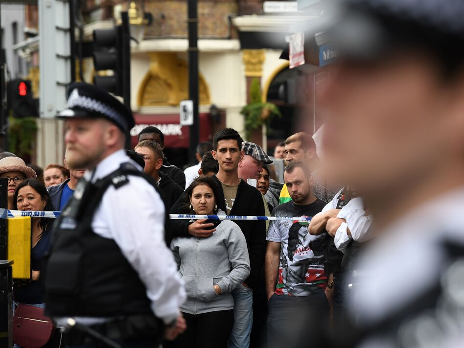 Londoners stand behind a cordon in the East Ham district on Sunday, following a police raid investigating Saturday's terror attacks in Central London. (Justin Tallis/AFP/Getty Images)