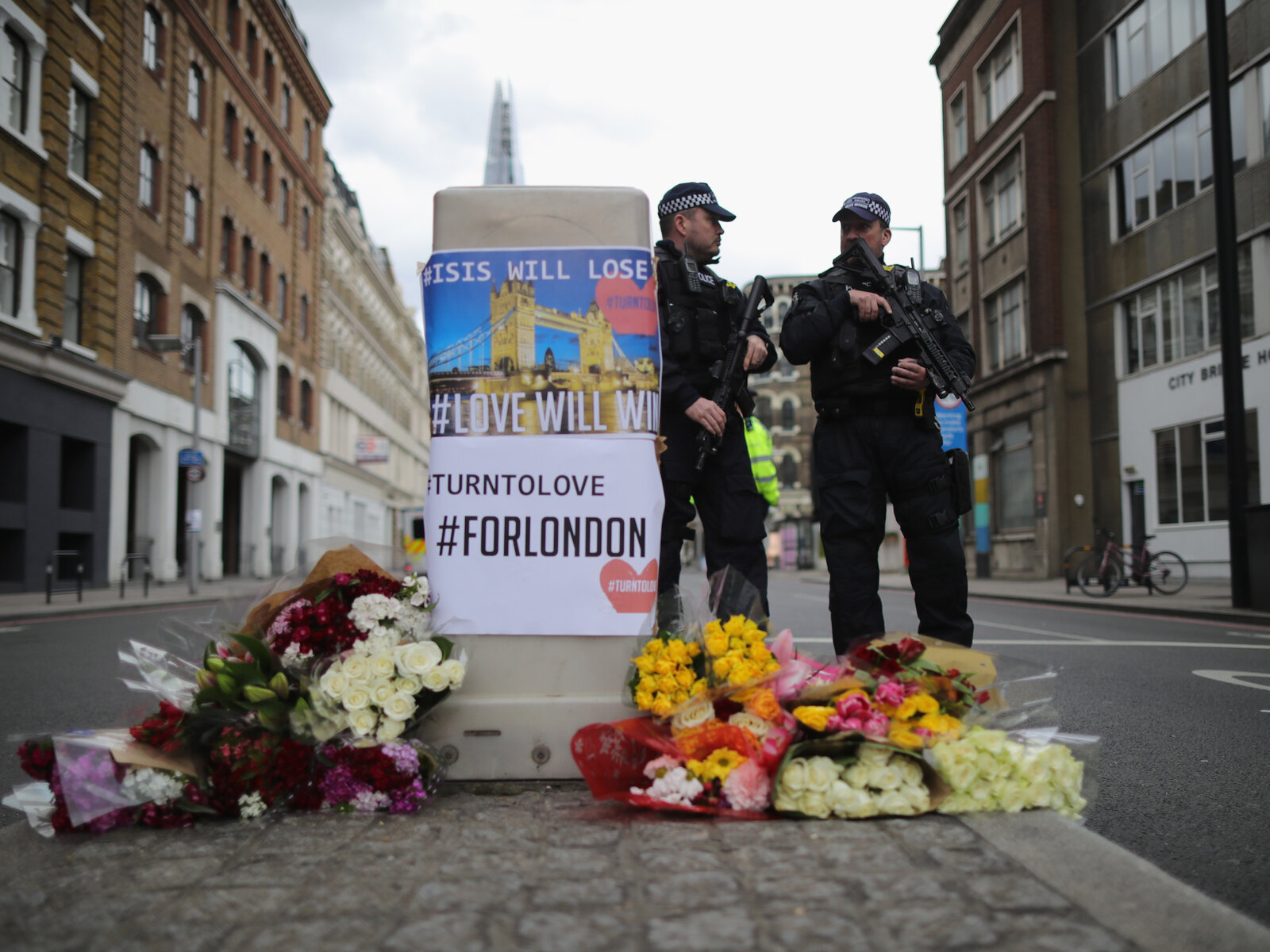 Police stand guard behind flowers left in memorial on Southwark Street near the scene of Saturday's terror attack in London. (Christopher Furlong/Getty Images)