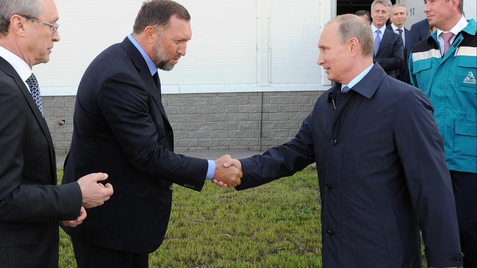 Businessman Oleg Deripaska (left) greets Russian President Vladimir Putin during a visit to a factory in Russia's Nizhny Novgorod region in September 2014. (Mikhail Klimentyev/AP)