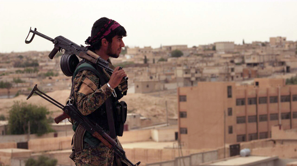 A fighter from the Syrian Democratic Forces, which is fighting to take control of Raqqa, looks toward the nearby town of Tabqa, Syria, in April.