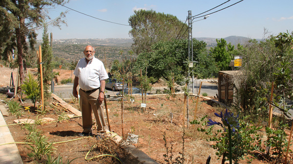 Ephraim Bluth, originally from New York, stands in the yard of his home in the West Bank settlement of Neve Tzuf, also known as Halamish.