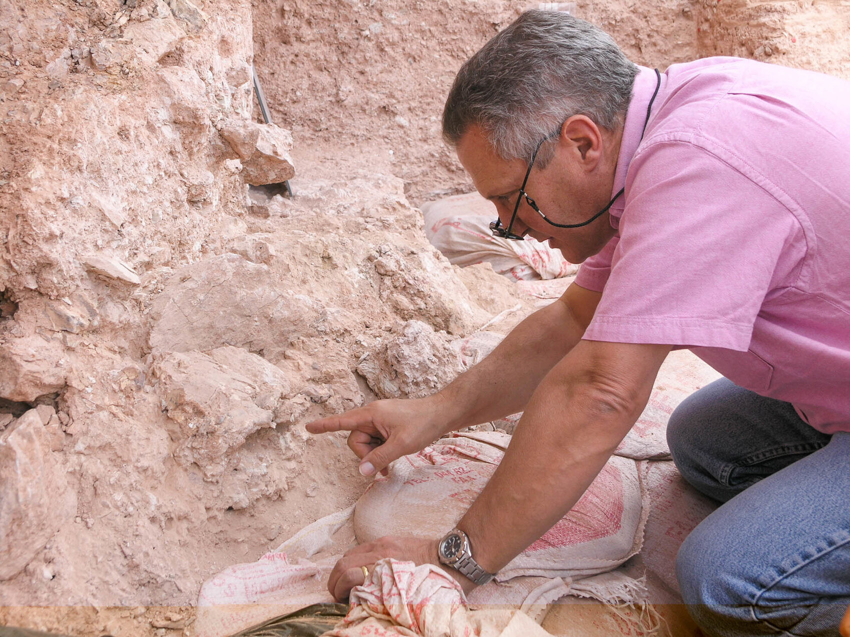 Max Planck Institute paleoanthropologist Jean-Jacques Hublin examines the new finds at Jebel Irhoud, in Morocco. The eye orbits of a crushed human skull more than 300,000 years old are visible just beyond his fingertip.     (Shannon McPherron/Nature)