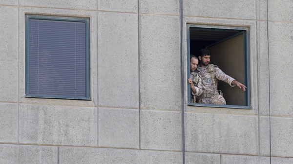 Men in military uniform stand at a window in the Iranian Parliament building following an attack on Wednesday in Tehran. More than a dozen people were killed and many more wounded during twin gun and suicide bomb attacks in Iran