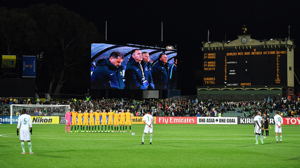 Australian soccer players (in yellow) observe a moment of silence for the victims of last week
