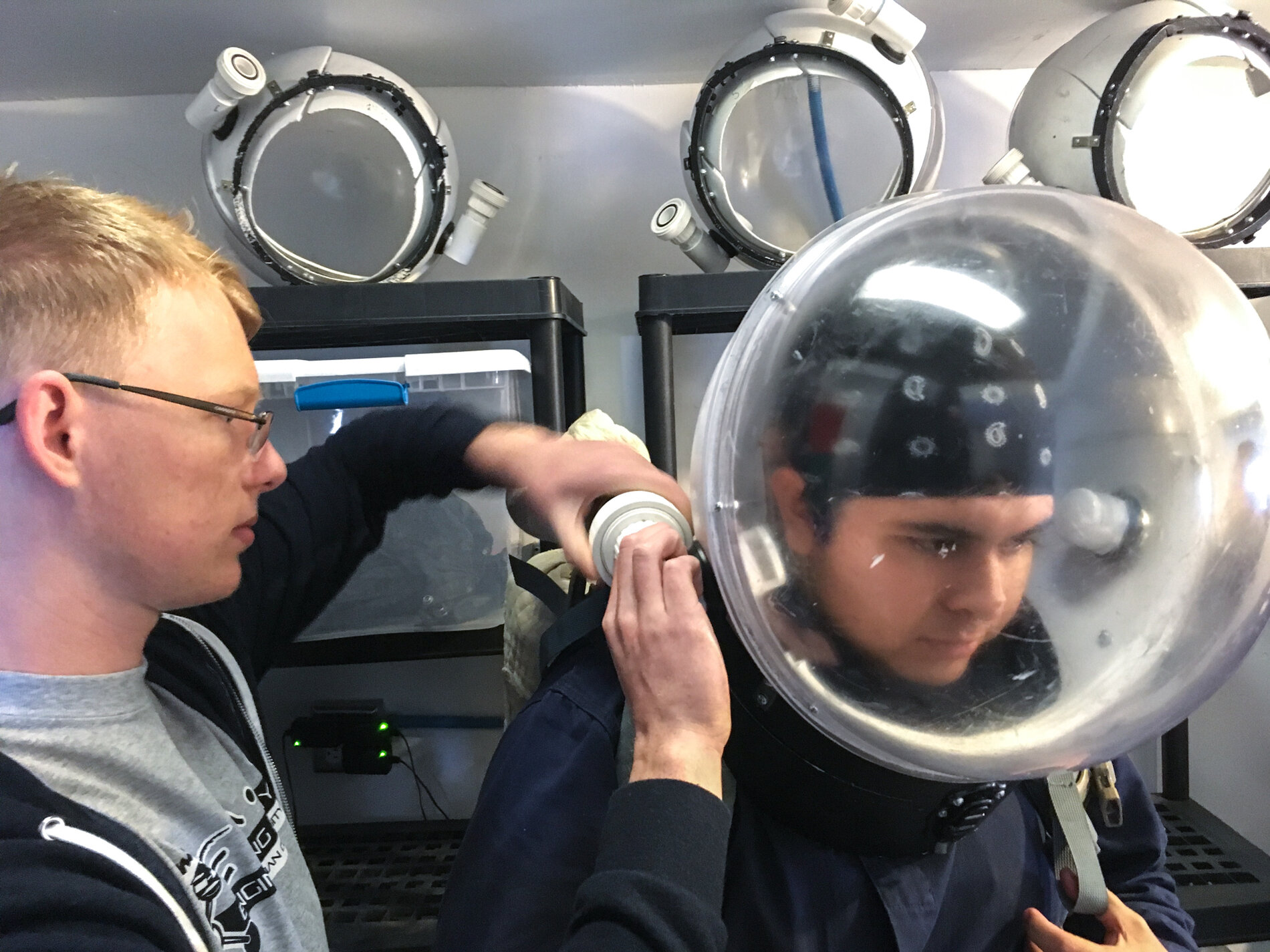 Quaas helps Espinoza suit up for a trip outside the station.     (Rae Ellen Bichell/NPR)