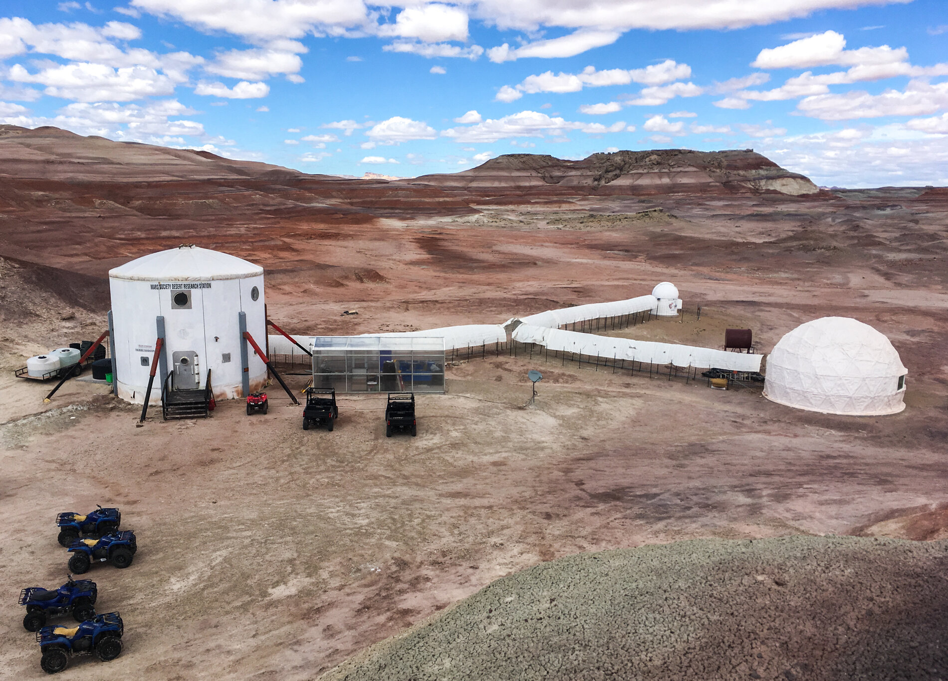 The Mars Desert Research Station in southern Utah. Living quarters are in the cylinder on the left, connected to the small observatory, science lab (far right) and a greenhouse.     (Rae Ellen Bichell/NPR)