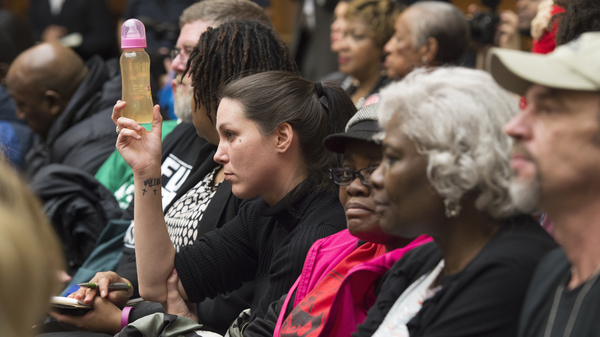 Flint, Mich. resident Jessica Owens holds up a baby bottle of water from her home in Flint while attending a hearing on Capitol Hill about the city
