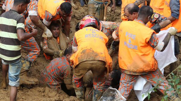 Bangladeshi firefighters pull a man from the mud Wednesday in Rangamati, after a landslide there killed scores of people. As rescue workers continue to search the area for missing people, authorities warn that the death toll is likely to rise.