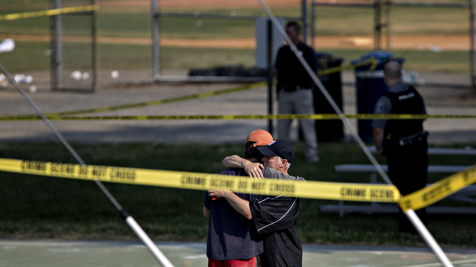 Two people embrace near the blocked-off crime scene in Alexandria, Va., where a congressman and several others were wounded in a shooting during a congressional baseball practice Wednesday. The suspected gunman has died, officials say. (Andrew Harrer/Bloomberg via Getty Images)