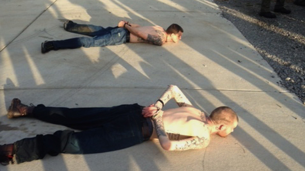 A Tennessee Bureau of Investigation photo shows the arrest of Georgia fugitives Donnie Rowe, top, and Ricky Dubose in Christiana, Tenn. The escaped inmates were captured Thursday in Tennessee after holding an elderly couple captive and leading police on a chase by car and foot, authorities said.