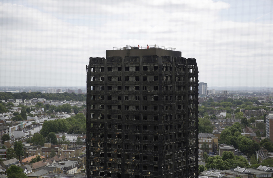 Emergency workers walk on the roof of the fire-gutted Grenfell Tower in London on Friday. (Matt Dunham/AP)
