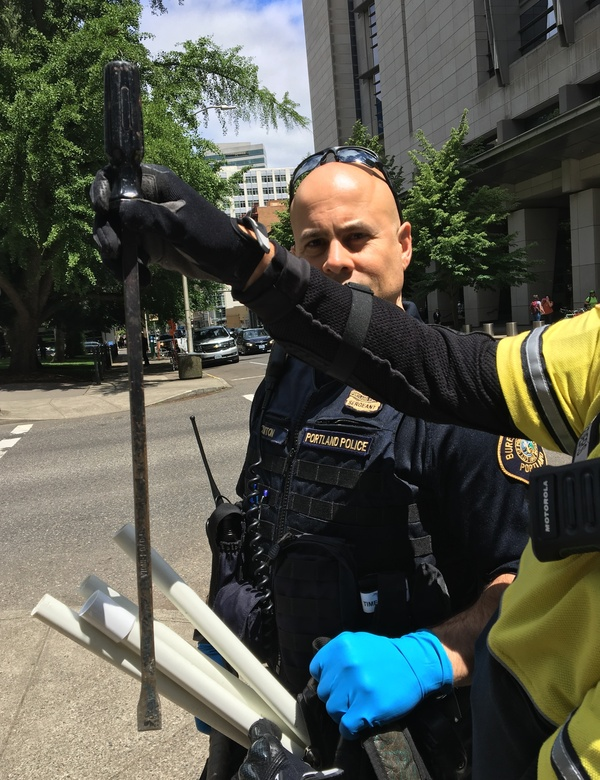 Portland police officers show a steel crowbar and pipes — weapons they seized from the Antifa-controlled zone during counterprotests in Portland, Ore., earlier this month.