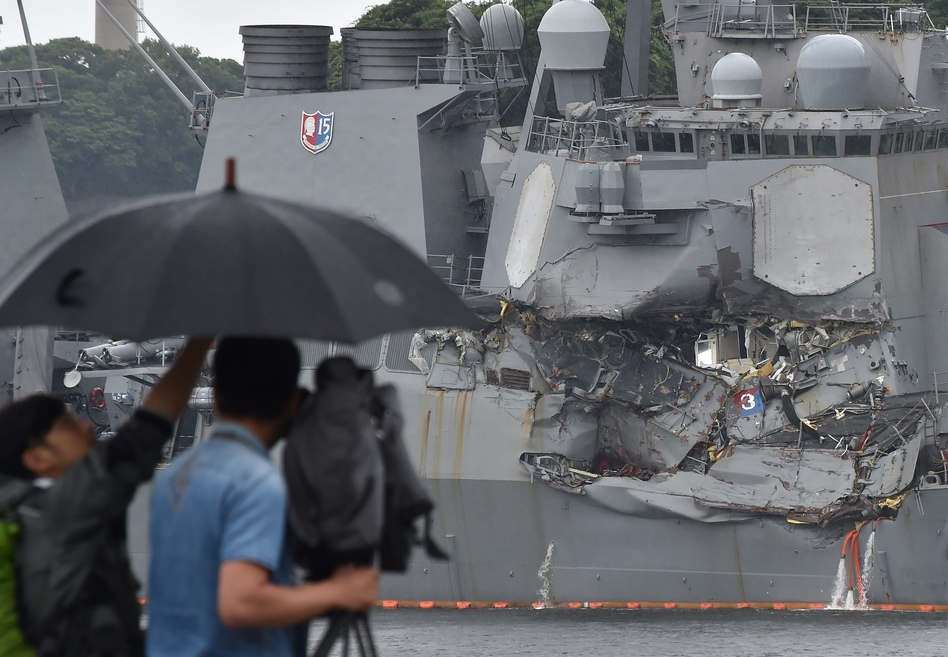 """A TV crew films the damage to the USS Fitzgerald at its port in Yokosuka, Japan, on Sunday. """"A number"""" of missing American sailors have been found dead in flooded areas of the destroyer, the U.S. Navy says. (Kazuhiro Nogi/AFP/Getty Images)"""