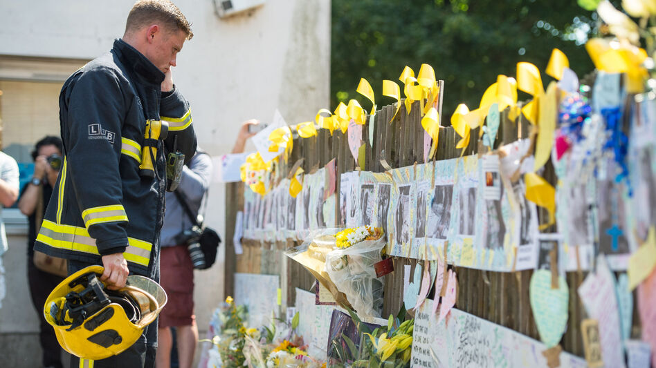 A firefighter looks at tributes to presumed victims of the Grenfell Tower fire, after observing a minute's silence at a community center near the apartment building in west London. (PA Images via Getty Images)