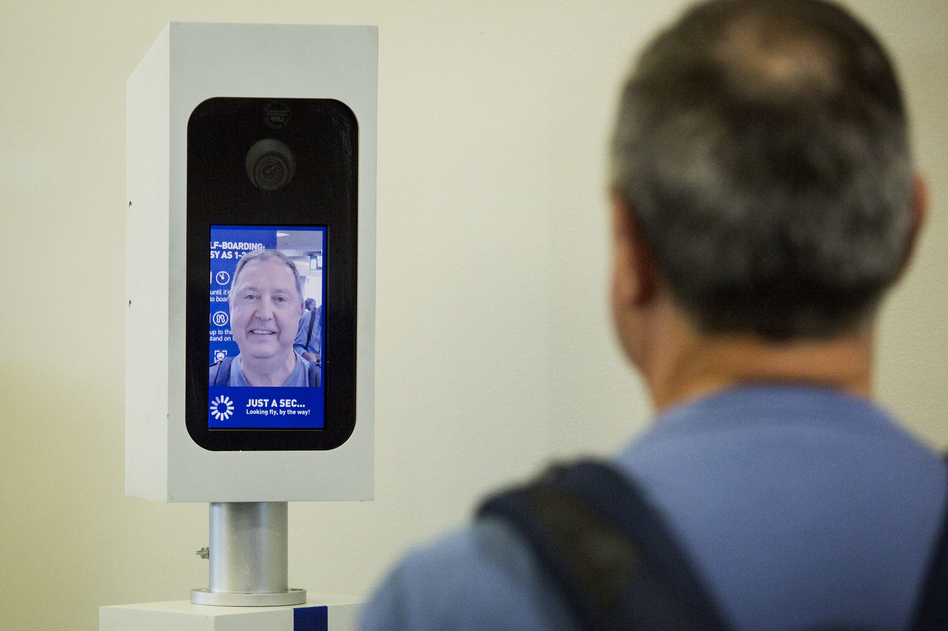 Charles Camiel looks into the camera for a facial recognition test before boarding his JetBlue flight to Aruba at Logan International Airport in Boston. (Robin Lubbock/WBUR)