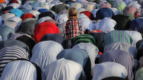 A child stands among the people taking part in Eid al-Fitr prayers in Bucharest, Romania. Members of the country