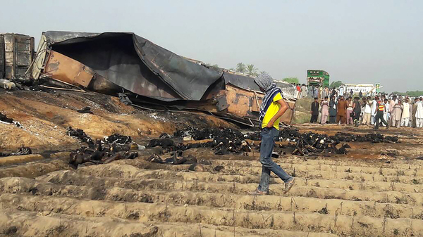 Local residents look at burnt bodies after an oil tanker caught fire on a highway Sunday in Pakistan.