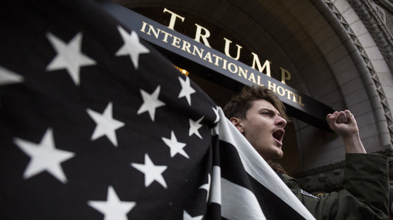 John Alfonso holds a black-and-white American flag during a protest at Trump International Hotel in Washington on Jan. 29. It's been the scene of multiple protests, as Trump continues to use the venue.