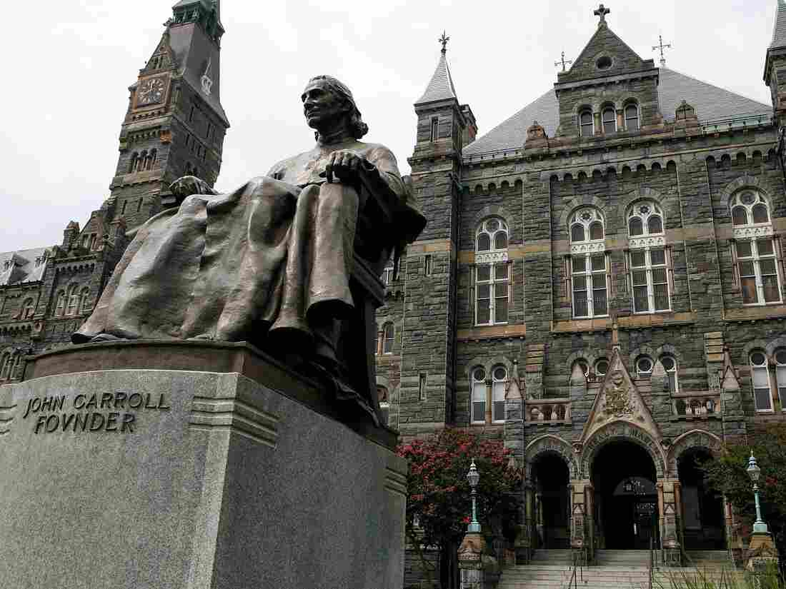 A statue of John Carroll, founder of Georgetown University, sits before Healy Hall on the school's campus. (Photo by Alex Wong/Getty Images)