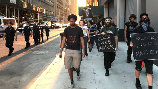 Mike Bento (center) is an organizer with NYC Shut It Down, a group which considers itself part of the Black Lives Matter movement. Escorted by NYPD officers, he leads a march in honor of a black transgender person who was recently killed in New York City.