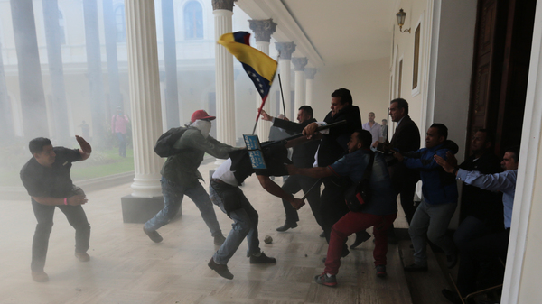 Opposition lawmakers brawl with pro-government militias trying to force their way into the National Assembly in Caracas on Wednesday.
