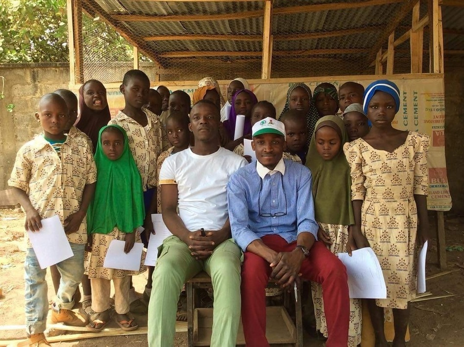 Aweofeso Adebola (in white shirt) and Ifeoluwa Ayomide (in cap) pose with some of their students. Zachariah Ibrahim, who dreams of being a pilot, stands behind the girl in the green hijab. Fatima Alidarunge, who wants to be a soldier to fight Boko Haram, is in the blue headgear. (Linus Unah for NPR)