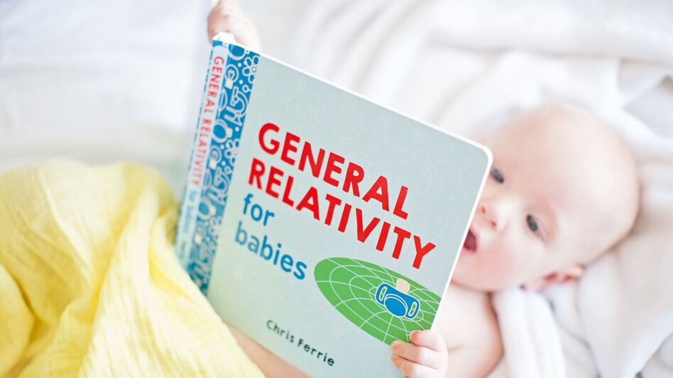 Milo Faust, 1, looks at a book from the <em>Baby University</em> series.