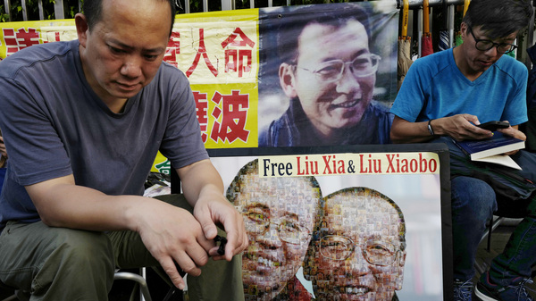 Protesters display portraits of jailed Chinese Nobel Peace laureate Liu Xiaobo during a demonstration outside the Chinese liaison office in Hong Kong on Wednesday. Liu has expressed the wish to leave China for medical treatment, but the government has refused. Foreign doctors who