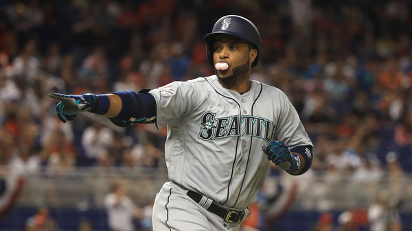 Robinson Cano of the Seattle Mariners blows a bubble as he rounds the bases after hitting a home run in the tenth inning of Tuesday