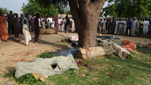 People gather on Wednesday to view the bodies of victims of an attack after suicide bombers detonated explosives in Maiduguri on Tuesday.