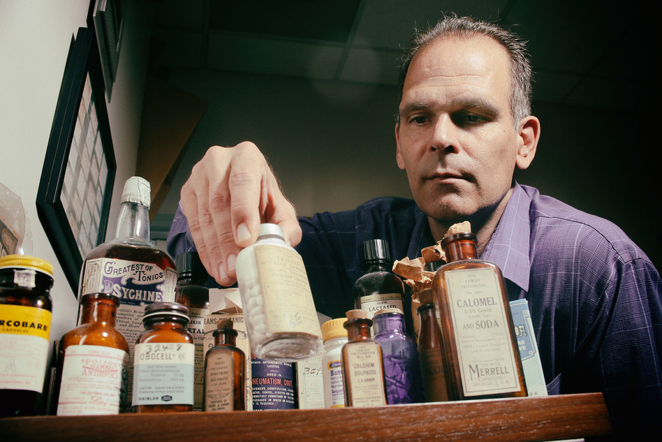 Lee Cantrell, an associate professor of clinical pharmacology at the University of California, San Diego, with a collection of vintage expired medications. (Sandy Huffaker for ProPublica)