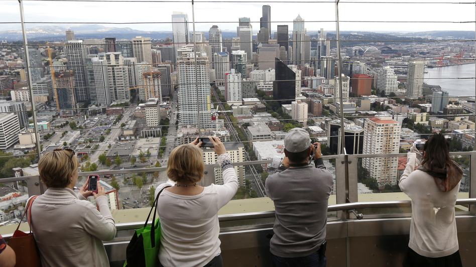 Seattle has adopted an income tax on high earners to address an affordability crisis stemming from the city's high tech boom, but tech workers are torn about being singled out. In this 2014 photo, tourists take photos atop the city's Space Needle.