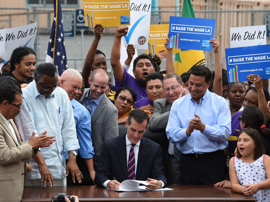 In 2015, Los Angeles Mayor Eric Garcetti (center) signs into law an ordinance raising the city's minimum wage to $15 an hour by 2020. Though California isn't one of them, 27 states have passed laws requiring cities to abide by state minimums. (Mark Ralston/AFP/Getty Images)