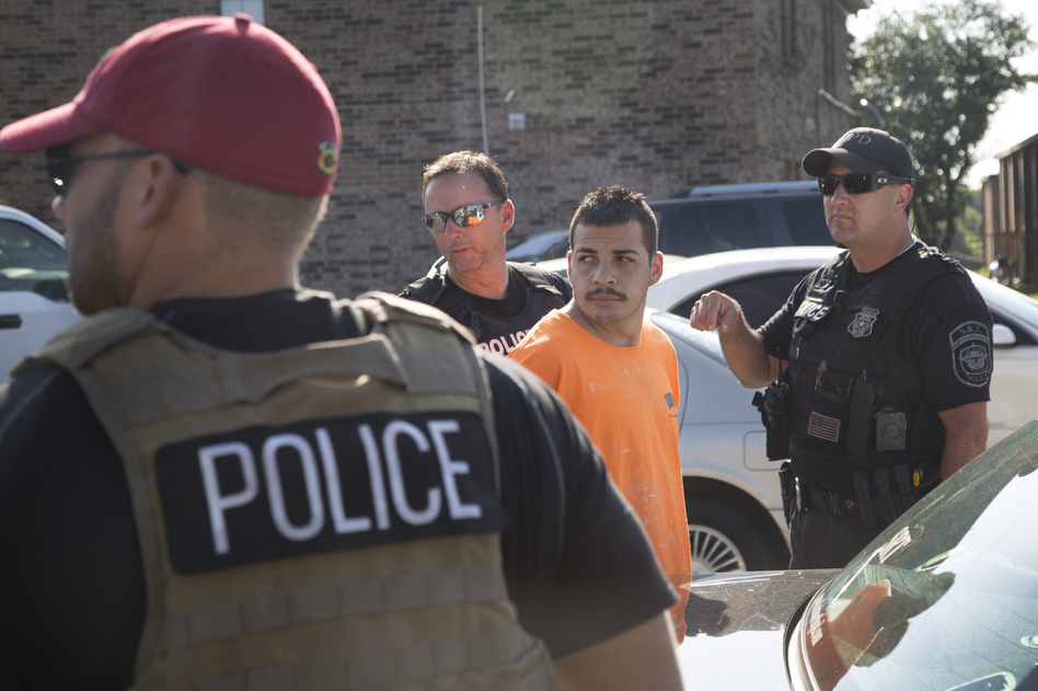 Immigration and Customs Enforcement officers and Fort Worth police officers detain an unauthorized immigrant from Mexico at an apartment complex. (Mito Habe-Evans/NPR)