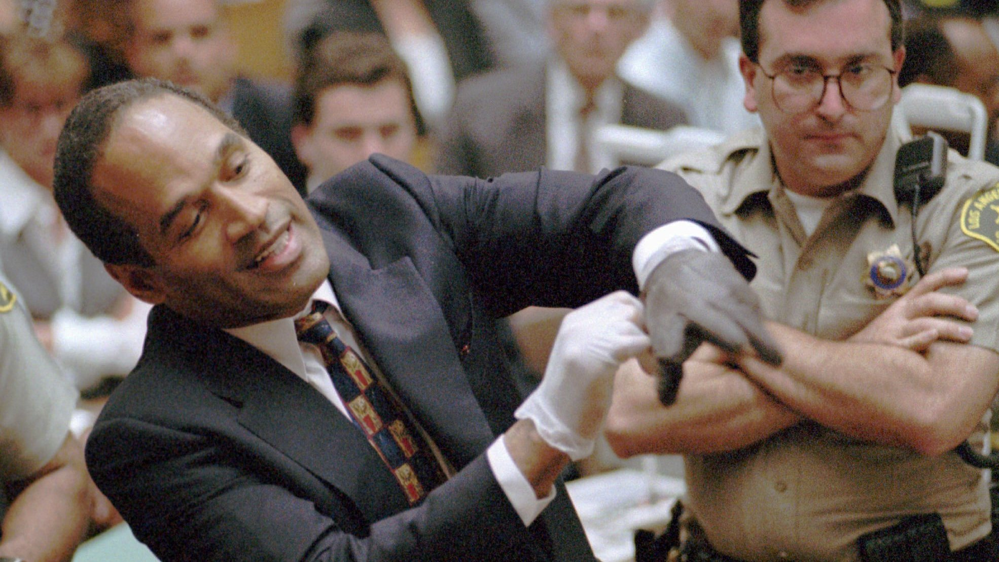 Murder defendant O.J. Simpson grimaces in July 1995 as he tries on one of the leather gloves prosecutors say he wore the night his ex-wife Nicole Brown Simpson and Ron Goldman were murdered. The trial transfixed the nation with a tale of a football hero turned accused murderer. (Sam Mircovich/AP)