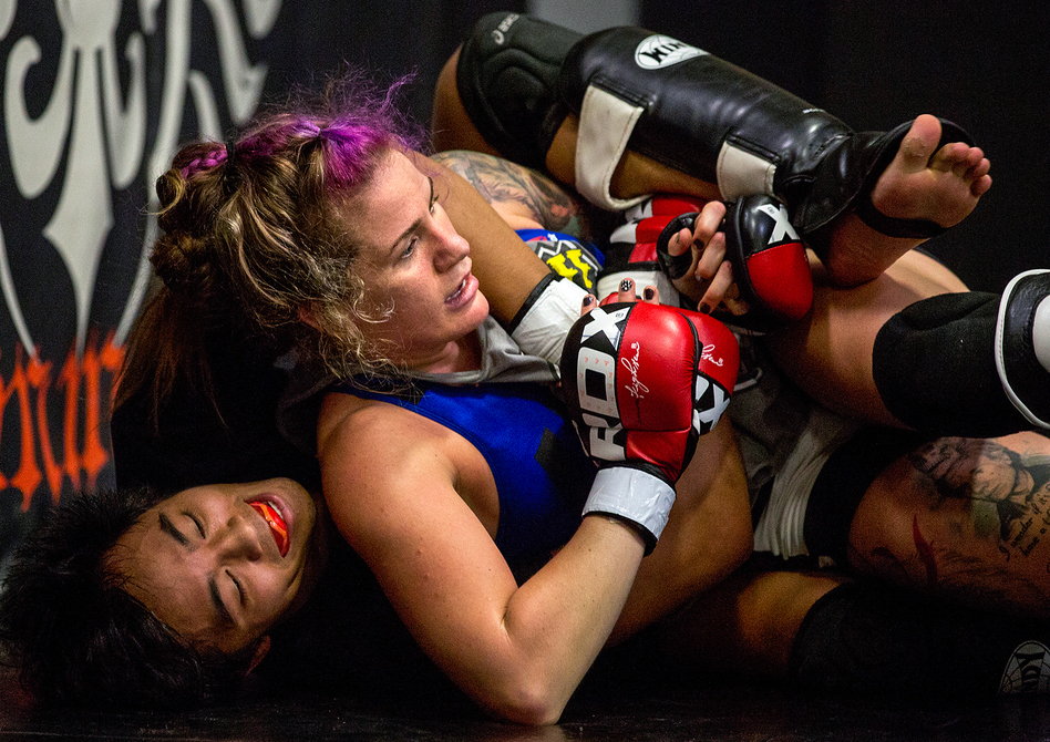 """Professional fighter Gina Mazany practices during a training session at Xtreme Couture Mixed Martial Arts in Las Vegas. She well remembers her first concussion — which came in her first fight. """"I was throwing up that night,"""" Mazany says. (Bridget Bennett for NPR)"""