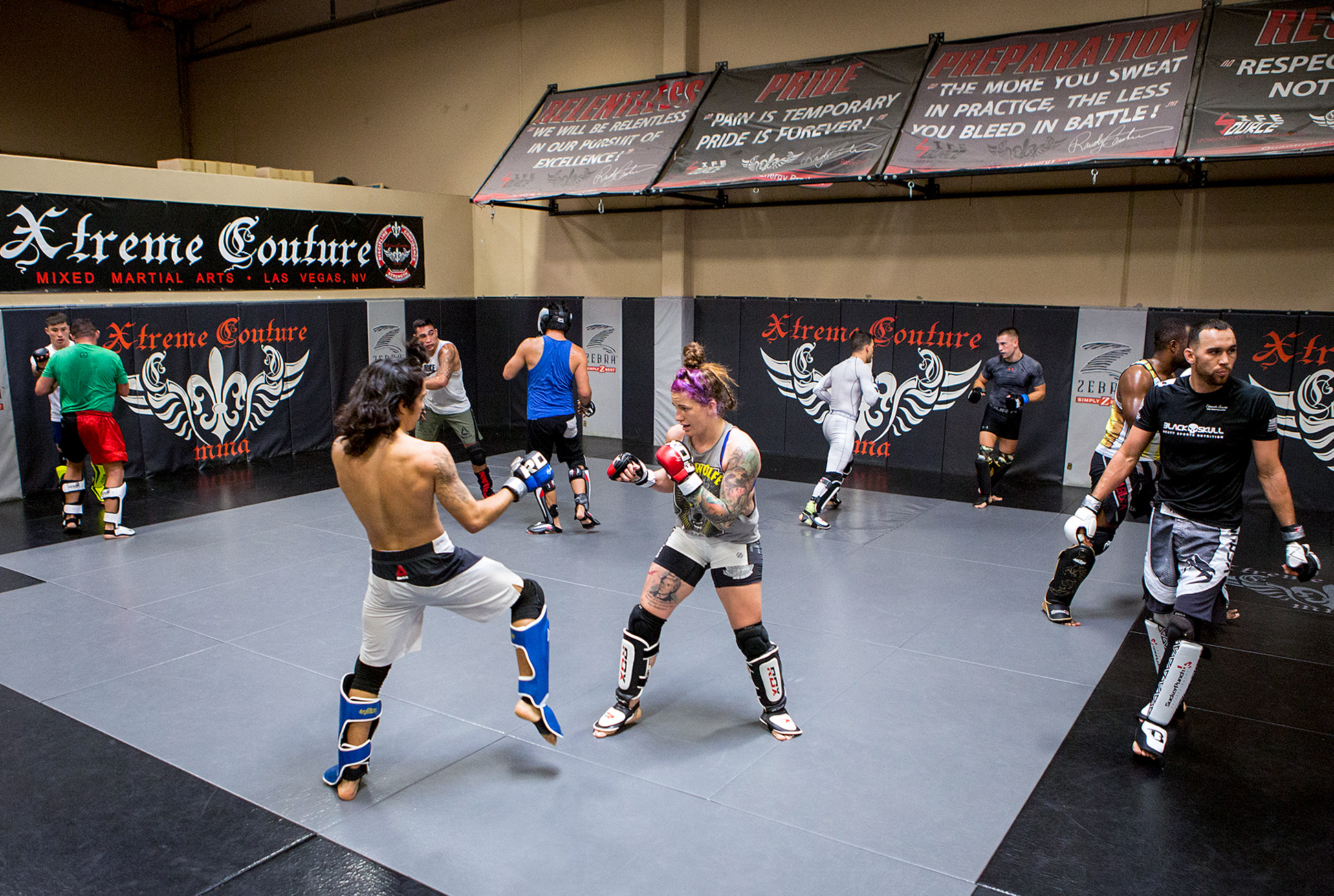Mazany, center, spars with Puni Pagaoa during a training session. Many women in MMA regularly spar with male fighters. (Bridget Bennett/For NPR)