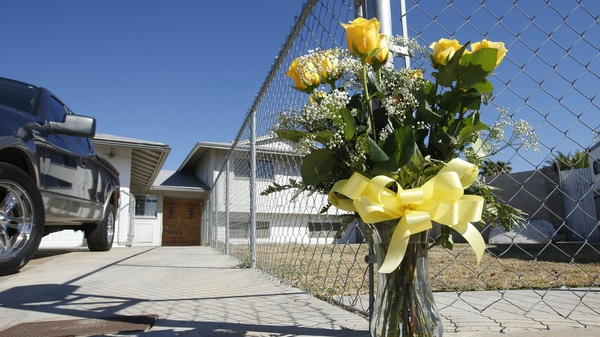 A lone bouquet of flowers stands in front of a home in Phoenix in 2013, after police said a man killed his wife, daughter and brother-in-law before killing himself. Half of all female homicide victims are murdered by a current or former romantic partner, the CDC says.