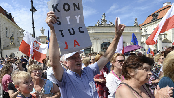 "A man holds a sign that says ""Constitution"" at a demonstration Monday in front of the presidential palace in Warsaw, Poland."