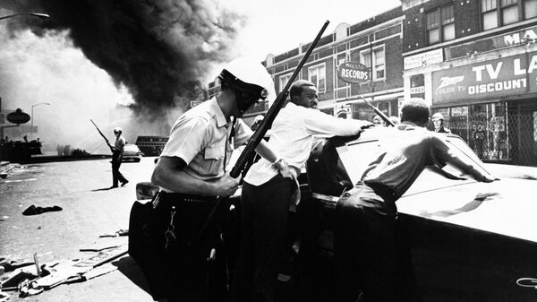A policeman searches black suspects in Detroit on July 25, 1967 as buildings burn in the distance.