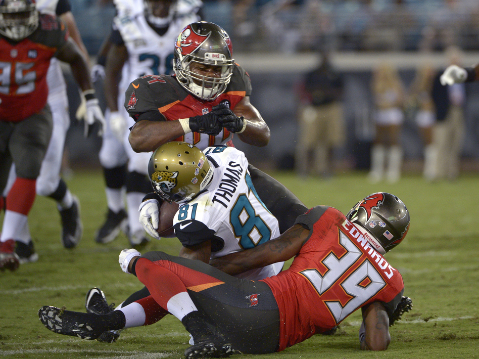 Jacksonville Jaguars wide receiver Lamaar Thomas (center) is hit in the head by Tampa Bay Buccaneers linebacker Brandon Magee as cornerback Kip Edwards helps make the tackle a 2014 preseason game. Magee was penalized for the hit. (Phelan M. Ebenhack/AP)
