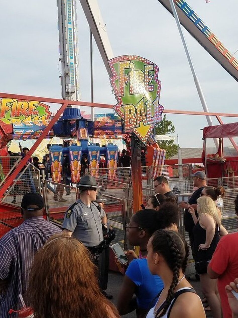 People watch as authorities respond after part of the Fire Ball ride broke off while in motion Wednesday night at the Ohio State Fair in Columbus, Ohio. One person was killed, and three were critically injured. (Justin Eckard/AP)
