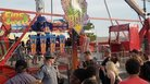 People watch as authorities respond near the Fire Ball ride after it part of it broke off while in motion Wednesday night at the Ohio State Fair in Columbus, Ohio. One person was killed and several were critically injured.