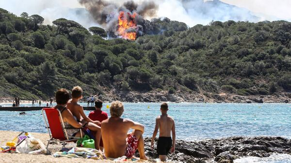 People look at a forest fire in La Croix-Valmer, near Saint-Tropez, as they sit on the beach. Thousands of French firefighters have been battling blazes that consumed swathes of land in southeastern France.